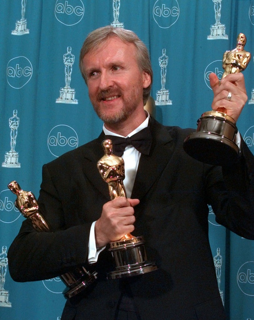 """James Cameron holds his three Oscars for the film """"Titanic"""" at the Shrine Auditorium in Los Angeles, Monday, March 23, 1998.  Cameron won the three awards for Best Director, Best Picture and Best Film Editing. (AP Photo/Reed Saxon)"""